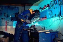 Συγκόλληση οξυγονοκολλητών με τη μάσκα συγκόλλησης και φανός στο εργαστήριο Στοκ Εικόνες