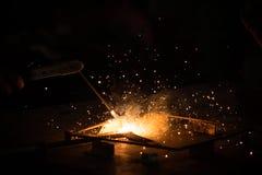 Συγκόλληση, μέταλλο που λειτουργεί στο σκοτεινό υπόβαθρο, με τη χρυσή φλόγα και bokeh των σπινθήρων Στοκ Εικόνες