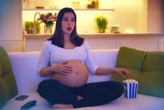 Συγκλονίζοντας κινηματογράφος προσοχής εγκύων γυναικών στο σπίτι μόνο Στοκ φωτογραφία με δικαίωμα ελεύθερης χρήσης