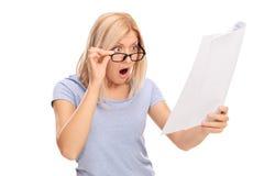 Συγκλονισμένη γυναίκα που εξετάζει τους λογαριασμούς στη δυσπιστία στοκ εικόνες