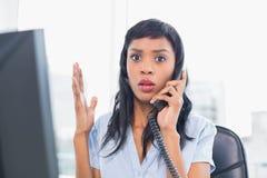 Συγκλονισμένη επιχειρηματίας που απαντά στο τηλέφωνο Στοκ φωτογραφίες με δικαίωμα ελεύθερης χρήσης