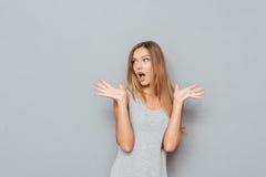 Συγκλονισμένη κατάπληκτη νέα γυναίκα με τα αυξημένα χέρια και το ανοιγμένο στόμα στοκ φωτογραφία με δικαίωμα ελεύθερης χρήσης