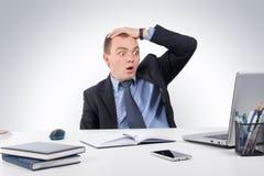 Συγκλονισμένος επιχειρηματίας με το φορητό προσωπικό υπολογιστή και έγγραφα στο γραφείο Στοκ εικόνες με δικαίωμα ελεύθερης χρήσης
