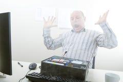Συγκλονισμένος επιχειρηματίας που εξετάζει τον καπνό που προκύπτει από τον υπολογιστή Στοκ εικόνα με δικαίωμα ελεύθερης χρήσης