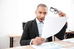 Συγκλονισμένος επιχειρηματίας που εξετάζει το έγγραφο και που κρατά eyeglasses Στοκ Εικόνες