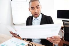 Συγκλονισμένος επιχειρηματίας που εξετάζει το έγγραφο και που κρατά eyeglasses Στοκ φωτογραφία με δικαίωμα ελεύθερης χρήσης