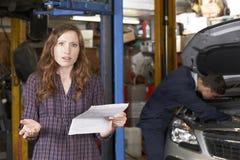 Συγκλονισμένος θηλυκός πελάτης που εξετάζει το γκαράζ Μπιλ Στοκ εικόνα με δικαίωμα ελεύθερης χρήσης