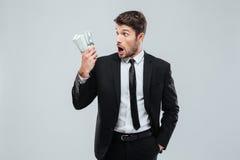 Συγκλονισμένος κατάπληκτος νέος επιχειρηματίας που στέκεται και που κρατά τα χρήματα Στοκ Φωτογραφίες