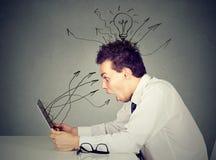 Συγκλονισμένος νεαρός άνδρας που εργάζεται στο lap-top στοκ εικόνες