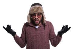 Συγκλονισμένος νεαρός άνδρας στα χειμερινά ενδύματα και το καπέλο γουνών Στοκ Φωτογραφίες