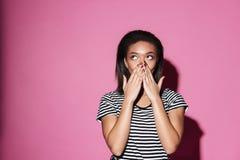 Συγκλονισμένο αφρικανικό κορίτσι που κοιτάζει μακριά και που καλύπτει το στόμα της στοκ εικόνες με δικαίωμα ελεύθερης χρήσης