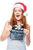 Συγκλονισμένο συναισθηματικό κορίτσι στο καπέλο santa με clapper Στοκ Φωτογραφίες