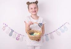 Συγχαρητήρια σε ευτυχές Πάσχα: το κορίτσι κρατά ένα καλάθι με τα χρωματισμένα αυγά από τον άσπρο τοίχο στοκ φωτογραφία
