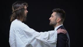 Συγχωρώντας Χριστός που βάζει το χέρι στον ώμο επιχειρηματιών, που φαίνεται μεταξύ τους, πίστη απόθεμα βίντεο