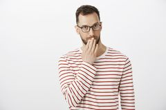 Συγχώρηση, πού είναι οι τρόποι μου Αδέξιο αμήχανο όμορφο αρσενικό με τη σκληρή τρίχα σε eyewear, καλύπτοντας το στόμα και κοιτάζο στοκ φωτογραφίες