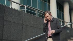 Συζήτησης ατόμων στο τηλέφωνο Περιστασιακός αστικός επαγγελματικός επιχειρηματίας που χρησιμοποιεί το smartphone που χαμογελά το  απόθεμα βίντεο