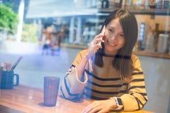 Συζήτηση γυναικών στο κινητό τηλέφωνο μέσα στον καφέ Στοκ φωτογραφία με δικαίωμα ελεύθερης χρήσης