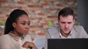 Συζήτηση επιχειρηματιών στην αμερικανική γυναίκα afro για τις πληροφορίες για την εργασία, που κοιτάζει για το lap-top απόθεμα βίντεο