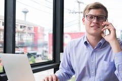 Συζήτηση επιχειρηματιών στο κινητό τηλέφωνο στο γραφείο κλήση νεαρών άνδρων στο sm Στοκ Φωτογραφίες