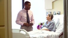 Συζητήσεις συμβούλων στον ανώτερο θηλυκό ασθενή στο δωμάτιο νοσοκομείων απόθεμα βίντεο