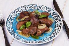 Συκώτι Sauteed με τα κρεμμύδια στο μπλε πιάτο Στοκ Φωτογραφία