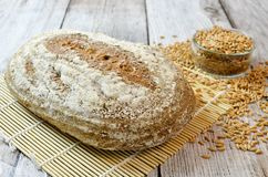 Συλλαβισμένο ψωμί με το συλλαβισμένο σιτάρι στον ξύλινο πίνακα Στοκ εικόνα με δικαίωμα ελεύθερης χρήσης