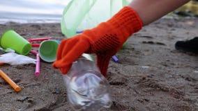 Συλλογή απορριμάτων στην παραλία Πλαστικό και συσκευασίες που διασκορπίζονται στην παραλία Ένα άτομο συλλέγει το πλαστικό Έννοια  φιλμ μικρού μήκους