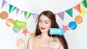 συμβαλλόμενο μέρος γενέθλια ευτυχή Ντεκόρ για τον εορτασμό Το αστείο κορίτσι χαμογελά, κλείνει το μάτι, χορεύει και κρατά στο πιά απόθεμα βίντεο