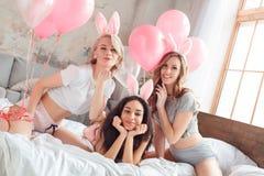 συμβαλλόμενο μέρος Νέες γυναίκες που φορούν τα αυτιά λαγουδάκι μαζί στο σπίτι στο κρεβάτι με τα μπαλόνια που στέλνουν το φιλί αέρ στοκ εικόνες