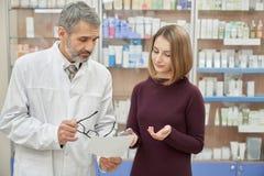 Συμβουλευτική γυναίκα φαρμακοποιών για τη συνταγή στο φαρμακείο στοκ εικόνα