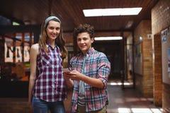 Συμμαθητές που χρησιμοποιούν το κινητό τηλέφωνο στο διάδρομο στο σχολείο στοκ εικόνες