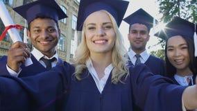 Συμμαθητές στο ακαδημαϊκό βασιλικό έμβλημα που παίρνει selfie την ημέρα βαθμολόγησης, επίτευγμα απόθεμα βίντεο