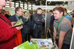 Συμμετέχοντες και επισκέπτες ενός ανοικτού έκθεση-πραγματικού προγράμματος στέγασης σεμιναρίου κτημάτων Στοκ Εικόνες