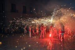 Συμμετέχοντες του θεάματος Correfocs (τρεξίματα πυρκαγιάς) που χορεύουν με το έλατο Στοκ Εικόνα