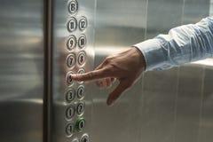 Συμπίεση του κουμπιού στον ανελκυστήρα Στοκ Εικόνες