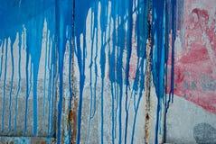 Συμπαγής τοίχος, λεκέδες του κόκκινου και μπλε χρώματος, γκράφιτι Στοκ εικόνες με δικαίωμα ελεύθερης χρήσης