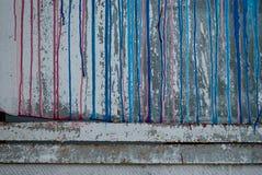 Συμπαγής τοίχος, λεκέδες του κόκκινου και μπλε χρώματος, γκράφιτι Στοκ Εικόνες