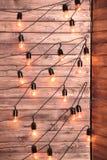 Συμπεριλαμβανόμενος διακοσμητικός και καμμένος βολβός στον ξύλινο τοίχο υποβάθρου στοκ φωτογραφία