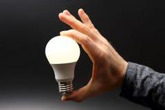 Συμπεριλαμβανόμενος οδηγημένος νέος λαμπτήρας στο ανθρώπινο χέρι στο σκοτεινό υπόβαθρο στοκ φωτογραφία με δικαίωμα ελεύθερης χρήσης