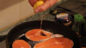 Συμπιέσεις μαγείρων του χυμού λεμονιών στα ψάρια απόθεμα βίντεο
