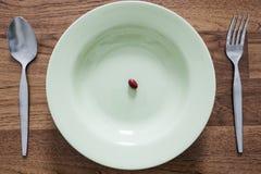 Συμπληρωματικά τρόφιμα στο πιάτο με το δίκρανο και κουτάλι στον ξύλινο πίνακα Στοκ εικόνες με δικαίωμα ελεύθερης χρήσης