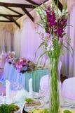 Συμπόσιο, πίνακες, λουλούδια, γυαλιά στοκ εικόνες