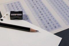 Συμπληρώνοντας έξω το φύλλο απάντησης με τη μείωση μολυβιών, sharpener και εγγράφου Στοκ εικόνα με δικαίωμα ελεύθερης χρήσης