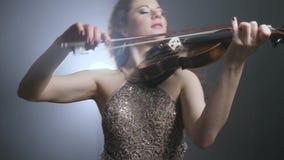 Συμφωνική ορχήστρα, ελκυστική μουσική δωματίων γυναικών παίζοντας στο βιολί σε φιλαρμονικό φιλμ μικρού μήκους