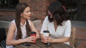 Συνάδελφοι γυναικών που μιλούν πέρα από ένα φλιτζάνι του καφέ επιχειρησιακές γυναίκες που κάθονται σε έναν θερινούς καφέ και μια  απόθεμα βίντεο