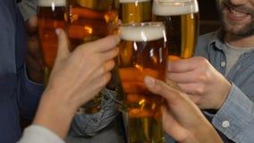 Συνάδελφοι με τα γυαλιά μπύρας που γιορτάζουν το επιτυχές πρόγραμμα στο μπαρ μετά από την εργασία απόθεμα βίντεο