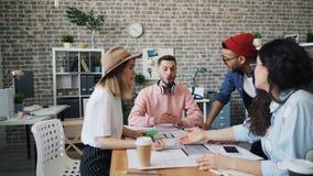 Συνάδελφοι που έχουν το επιχείρημα που συζητά την επιχείρηση στην εργασία που εξετάζει την οικοδόμηση του σχεδίου φιλμ μικρού μήκους