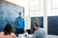 Συνάδελφοι που διοργανώνουν μια συνεδρίαση μαζί σε ένα σύγχρονο γραφείο Στοκ Εικόνα