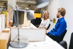 Συνάδελφοι που επικοινωνούν καθμένος στο γραφείο τους Στοκ Εικόνες