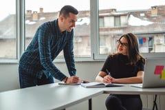 Συνάδελφοι που χαμογελούν ο ένας στον άλλο στο γραφείο εργαζόμενοι στοκ φωτογραφίες